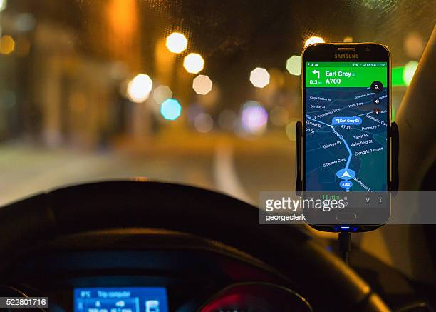 Using smartphone SatNav at night for driving directions.