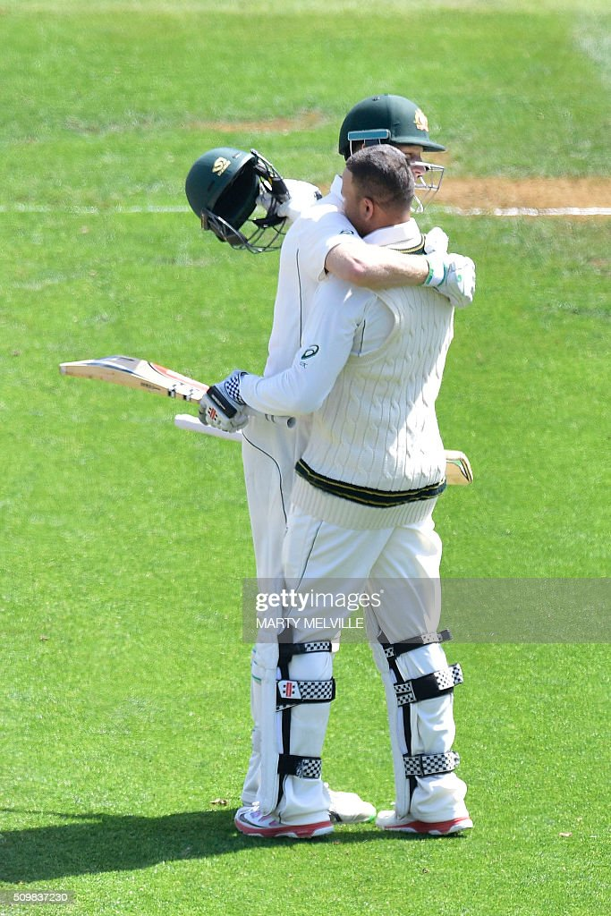 Usman Khawaja (R) celebrates 100 runs with team mate Adam Voges of Australia during day two of the first cricket Test match between New Zealand and Australia at the Basin Reserve in Wellington on February 13, 2016. AFP PHOTO / MARTY MELVILLE / AFP / Marty Melville