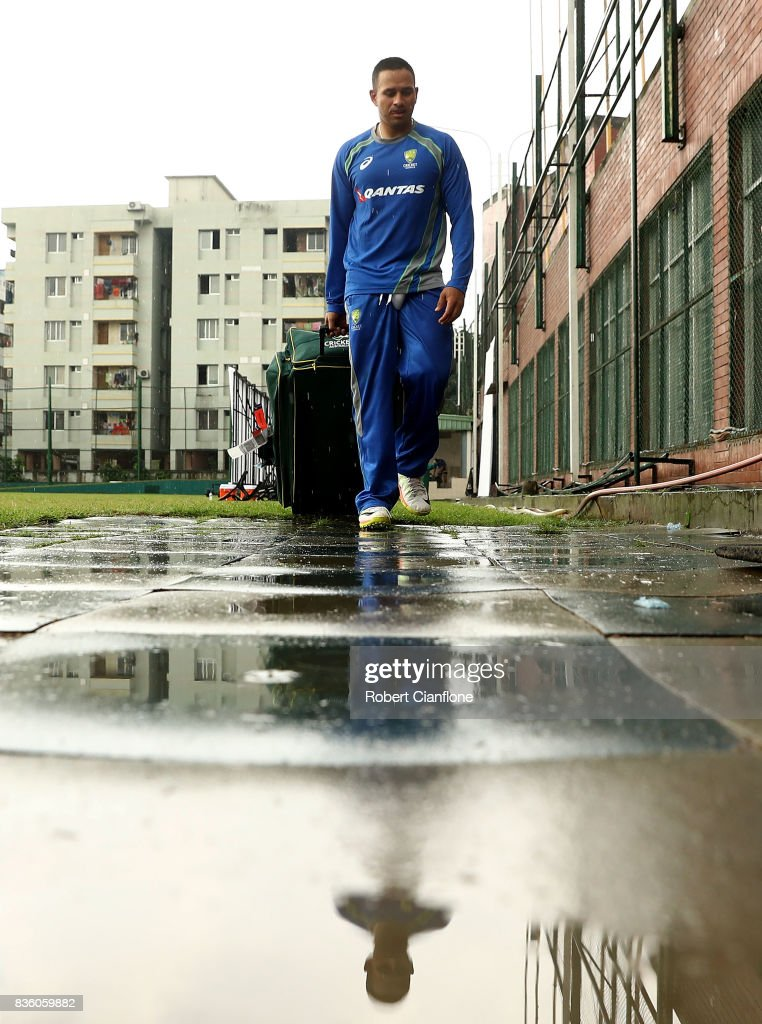 Usman Khawaja of Australia walks off the ground as rain falls during an Australian Test team nets session at Sher-E Bangla National Cricket Stadium on August 21, 2017 in Dhaka, Bangladesh.