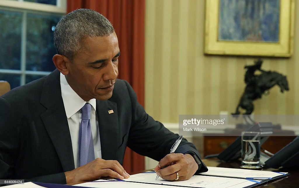 U.S.President Barack Obama signs a rescue package bill for Puerto Rico which is facing more than $70 billion in debt, in the Oval Office at the White House, June 30,2016 in Washington, DC.
