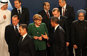 President Barack Obama talks to German Changellor Angela Merkel during a group photo session at the G20 Summit on November 3 2011 in Cannes France...
