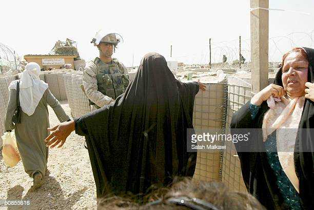 Ssoldier check an Iraqi woman outside the Abu Ghraib prison as arraignments began inside the 'Green Zone' on May 19 2004 in Baghdad Iraq for three...