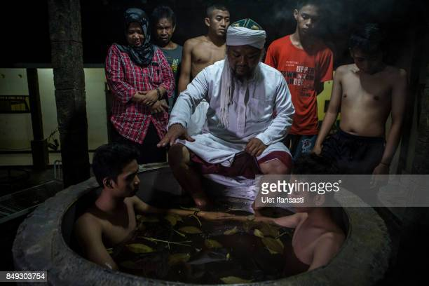 Ustad Ahmad Ischsan Maulana the head of Nurul Ichsan Al Islami traditional rehabilitation centre prays with recovering drug addicts who are immersed...