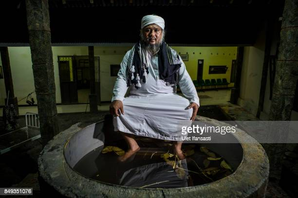 Ustad Ahmad Ischsan Maulana the head of Nurul Ichsan Al Islami traditional rehabilitation centre poses for photograph in a hot water herbal bath on...