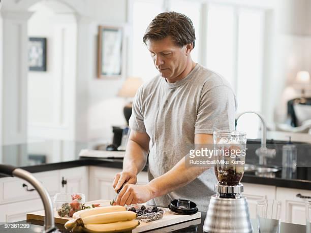 USA, Utah, Alpine, mature man cutting fruits in kitchen