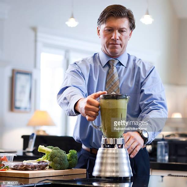 USA, Utah, Alpine, mature man preparing vegetable drink