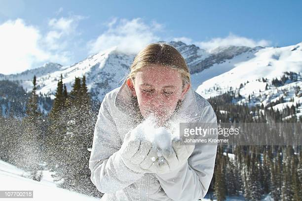 USA, Utah, Alta, Girl (10-11) blowing snow in mountains
