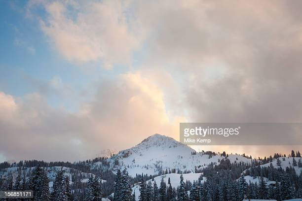 USA, Utah, Big Cottonwood Canyon, Snow covered mountain peak with late evening sky