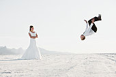 USA, Utah, Boneville Salt Flats, Bride watching groom performing backflip in desert