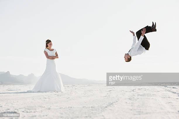 USA, Utah, Boneville Salt Flats, Bride watching groom performing backflip in desert