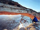 USA, Utah, Canyonlands National Park, man looking through Mesa Arch