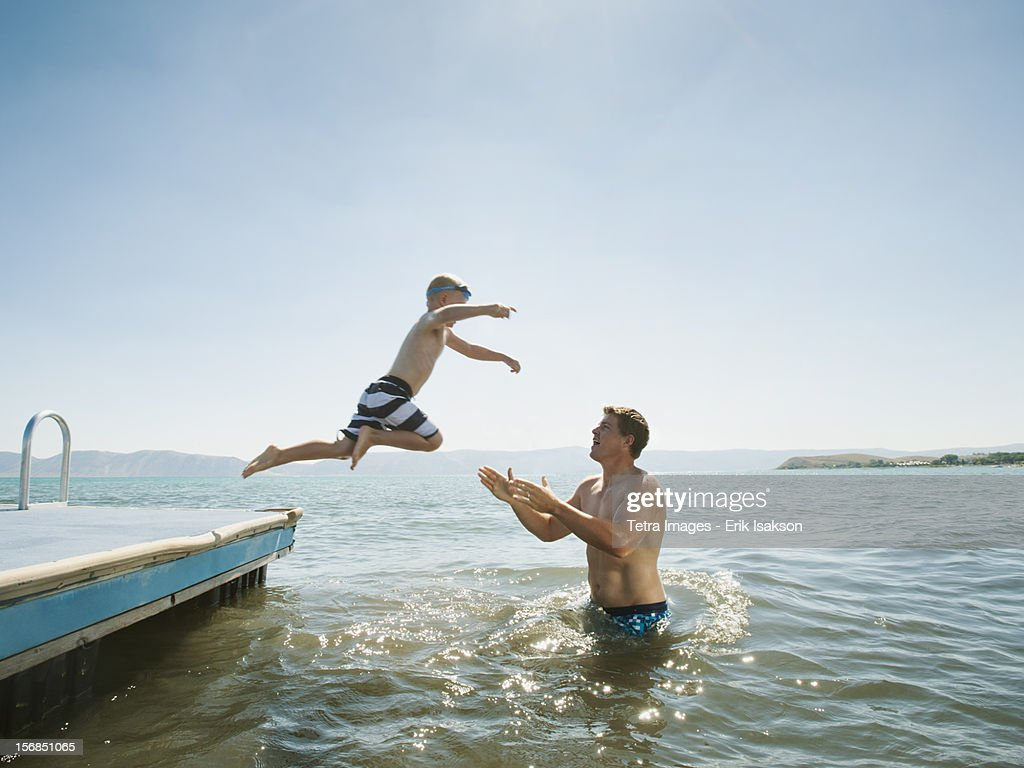 USA, Utah, Garden City, boy (4-5) jumping into lake caught by his father