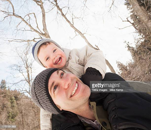 USA, Utah, Highland, Young man carrying his son (12-17 months) on shoulders