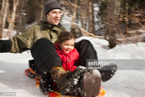 USA, Utah, Highland, Young man sledding with girl (2-3)