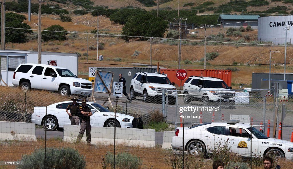 Utah Highway Patrol and National Security Agency (NSA) security personnel watch over protesters at the entrance of the new NSA Utah Data Center being built in Bluffdale, Utah, U.S., on Thursday, July 4, 2013. Russian President Vladimir Putin said NSA whistleblower Edward Snowden must quit hurting American interests if he wants to remain in Russia, after an official said the fugitive applied for asylum there. Photographer: George Frey/Bloomberg via Getty Images