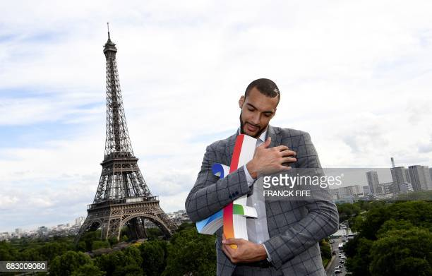 Utah Jazz's French centre Rudy Gobert holds the logo of Paris bid for the 2024 Olympic Games in front of the Eiffel tower as the International...
