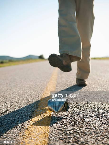 USA, Utah, Kanosh, Man kicking tin can on otherwise empty road