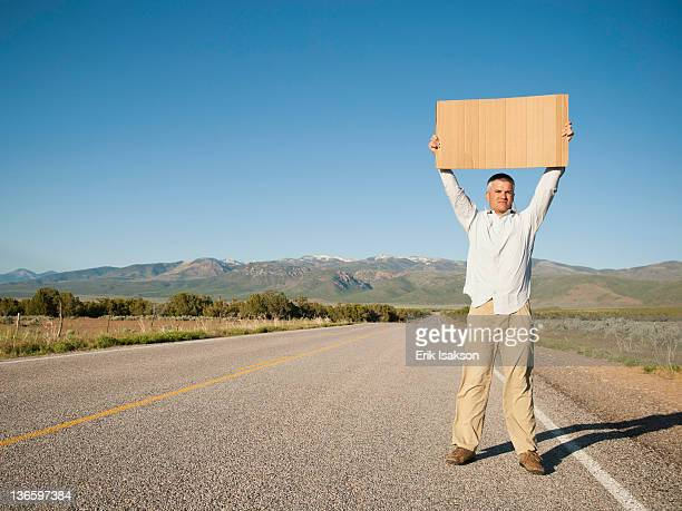USA, Utah, Kanosh, Mid-adult man hitch-hiking in barren scenery