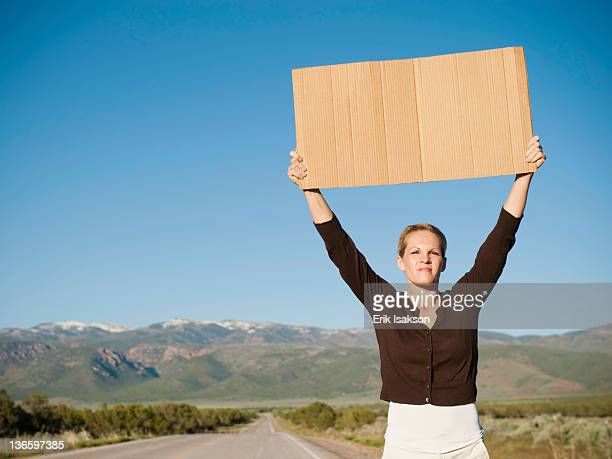 USA, Utah, Kanosh, Mid-adult woman hitch-hiking in barren scenery