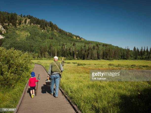 USA, Utah, Lake City, Boy (4-5) with grandfather walking on boardwalk through wetland