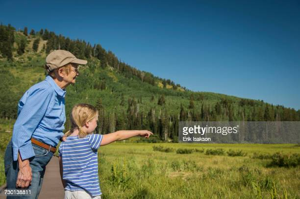 USA, Utah, Lake City, Girl (4-5) with grandmother standing on boardwalk by wetland