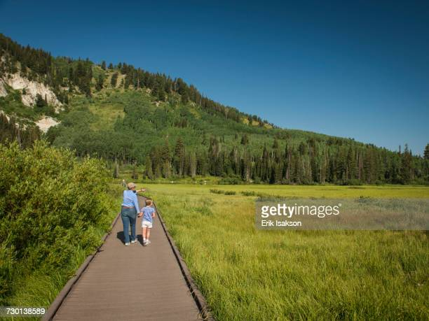 USA, Utah, Lake City, Girl (4-5) with grandmother walking on boardwalk through wetland