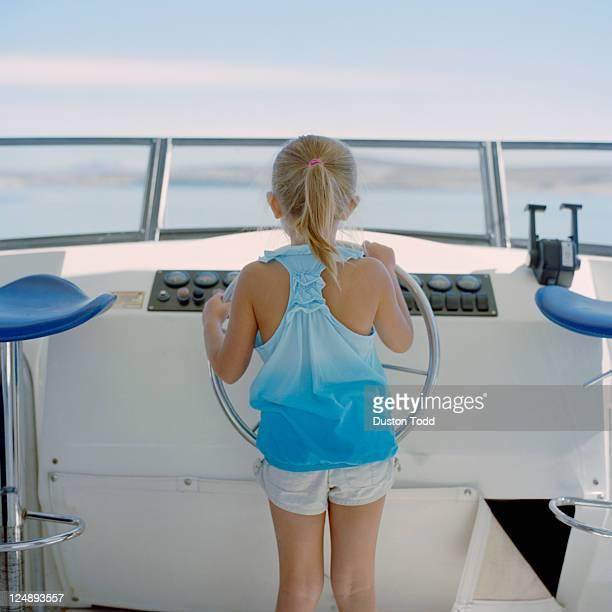 USA, Utah, Lake Powell, Girl (6-7) at wheel of sailboat, rear view