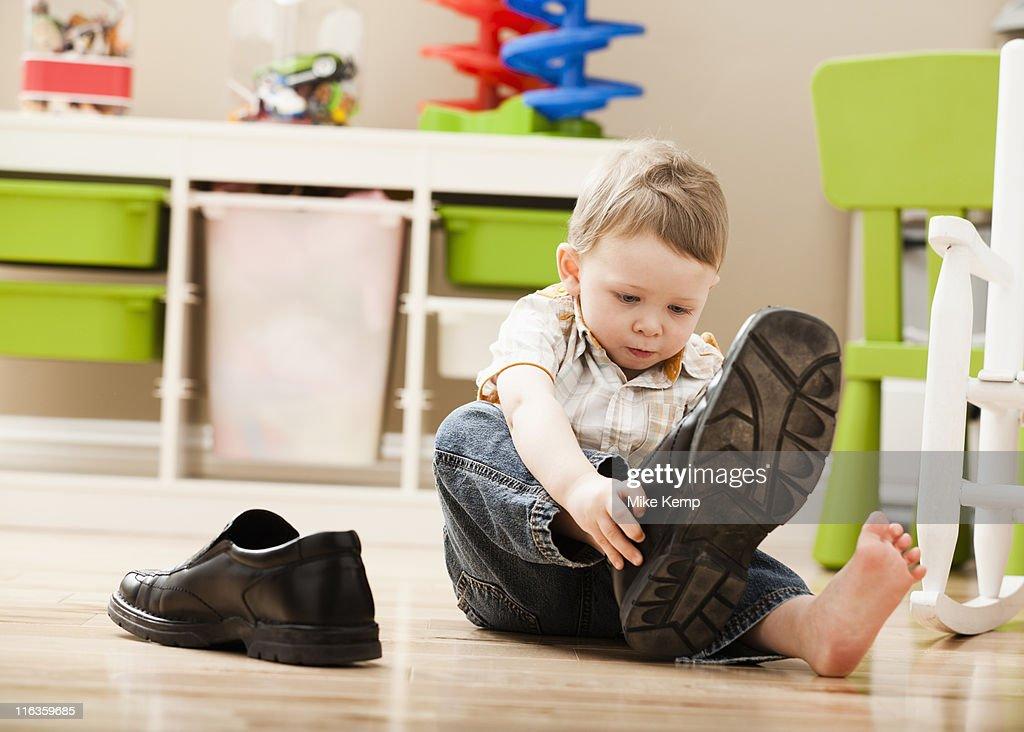 USA, Utah, Lehi, Boy (2-3) putting on dad's shoes