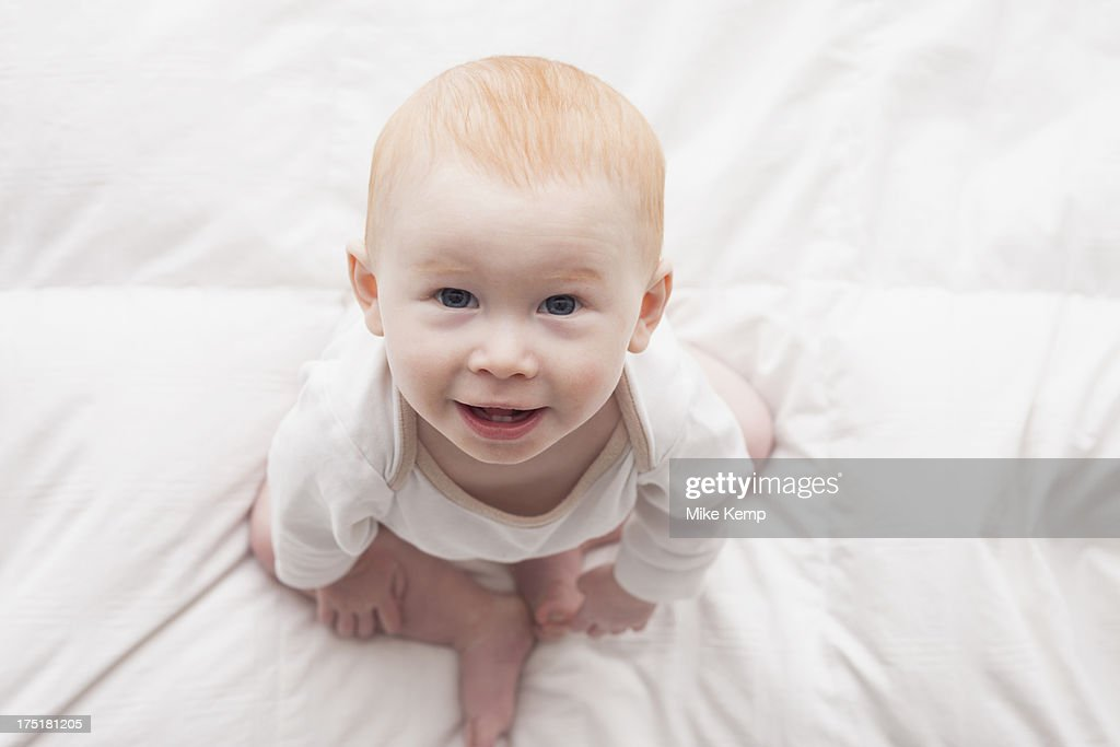 USA, Utah, Lehi, Directly above portrait of baby boy (18-23 months) sitting on duvet and looking at camera : Stock Photo