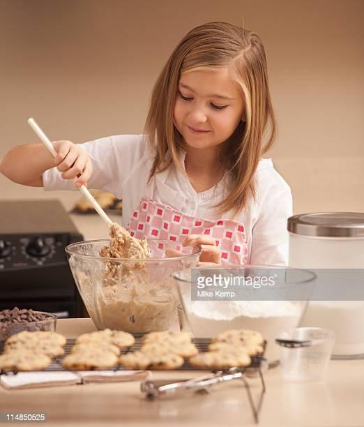 USA, Utah, Lehi, Girl (10-11) baking biscuits in kitchen
