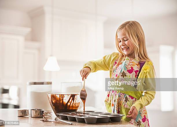 USA, Utah, Lehi, Girl (6-7) baking cupcakes