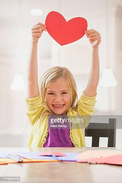 USA, Utah, Lehi, Girl (6-7) holding red paper heart