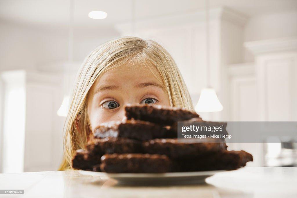 USA, Utah, Lehi, Girl (6-7) looking at heap of brownies