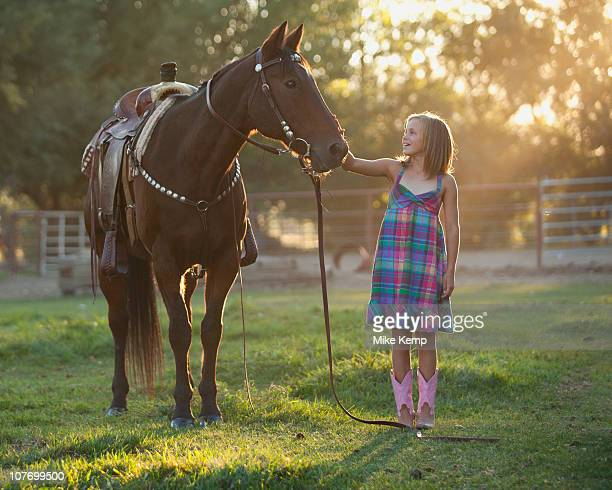 USA, Utah, Lehi, Girl (8-9) stroking horse in paddock