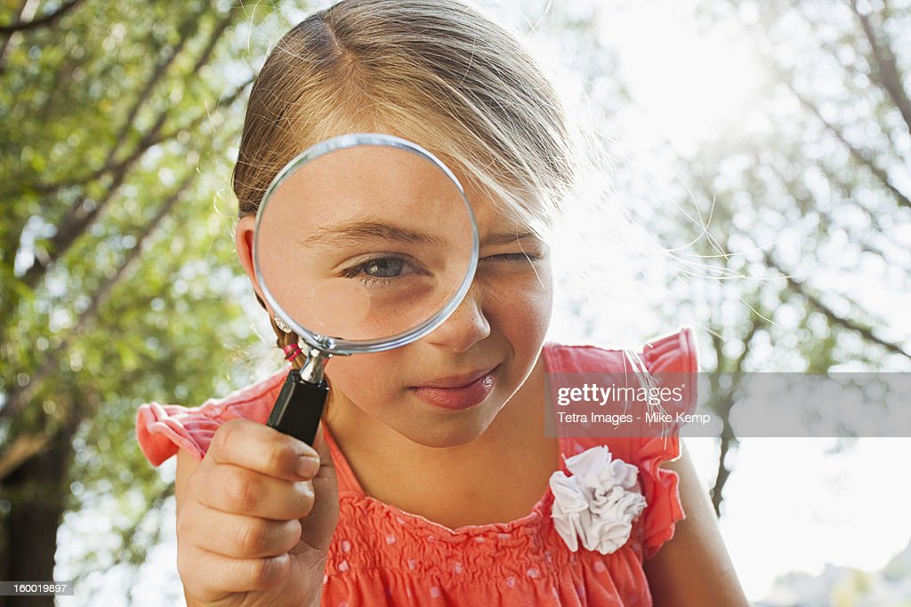 USA, Utah, Lehi, Little girl (6-7) looking through magnifying glass
