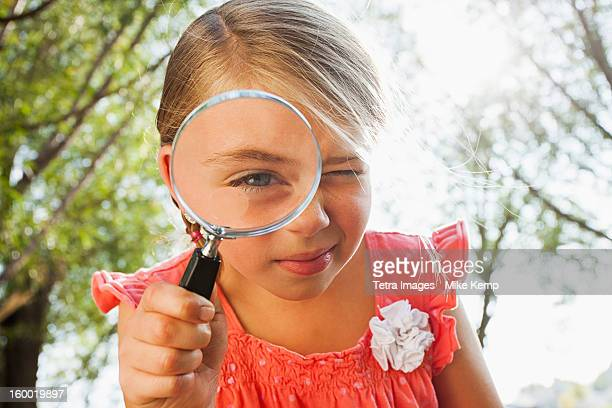 USA, Utah, Lehi, Little girl (6-7) looking through magnifying glass