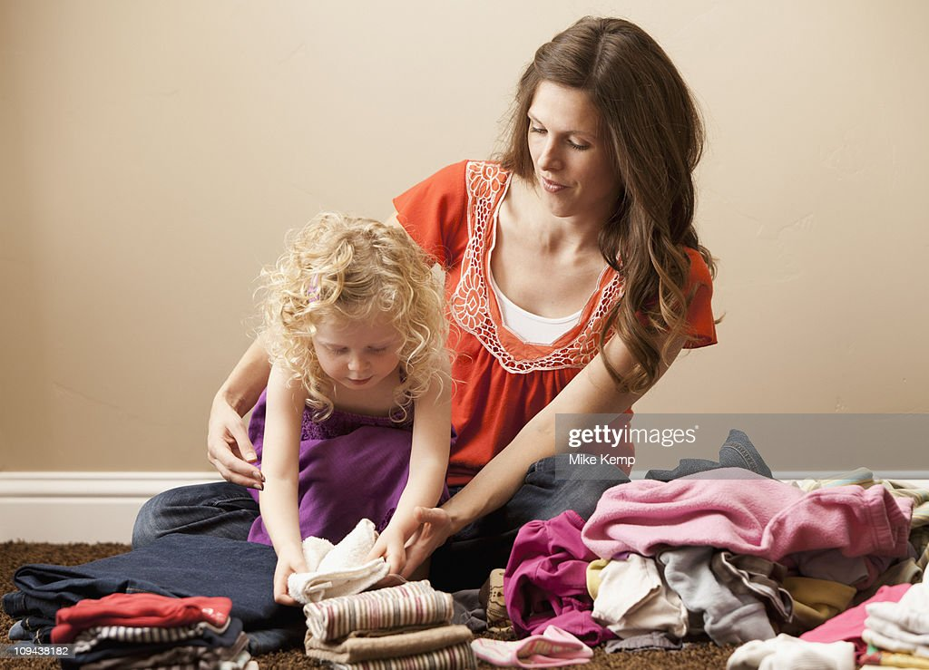 USA, Utah, Lehi, mother and daughter (2-3) folding laundry : Stock Photo