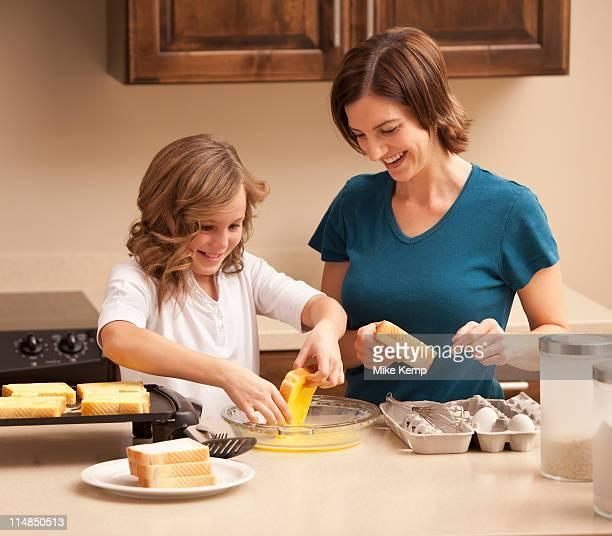 USA, Utah, Lehi, Mother preparing breakfast with daughter (10-11) in kitchen