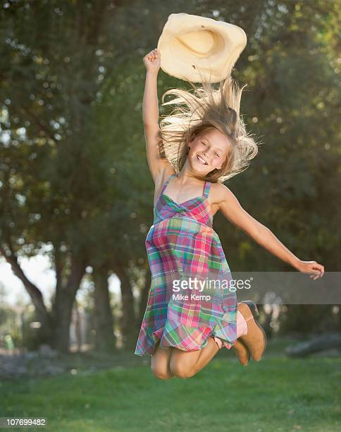 USA, Utah, Lehi, Portrait of smiling cowgirl (8-9) jumping