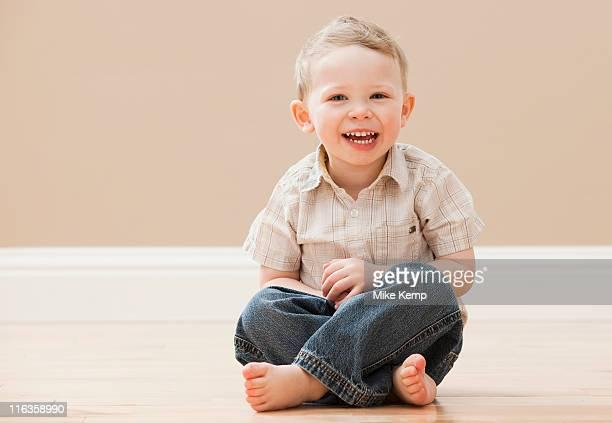 USA, Utah, Lehi, Portrait of young boy (2-3) sitting cross-legged