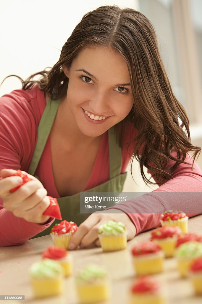 usa utah lehi portrait of young woman decorating cupcakes in kitchen stock