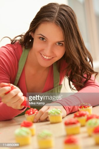 Woman Decorating Cupcakes woman decorating cupcakes with sugar sprinkles stock photo | getty