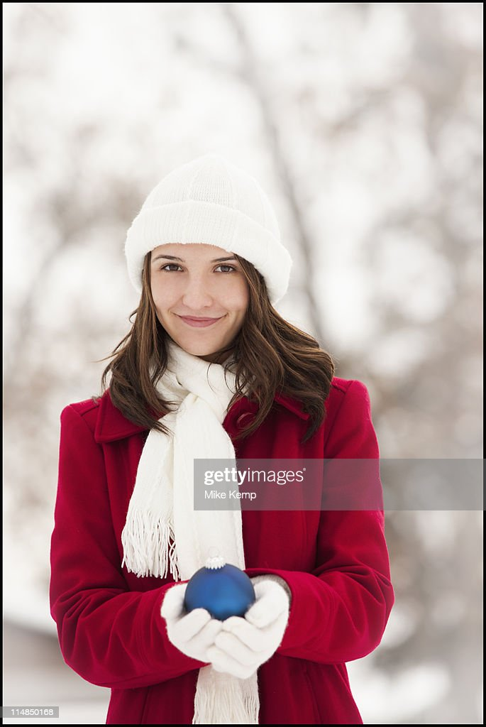 USA, Utah, Lehi, Portrait of young woman holding Christmas bauble outdoors : Stock Photo