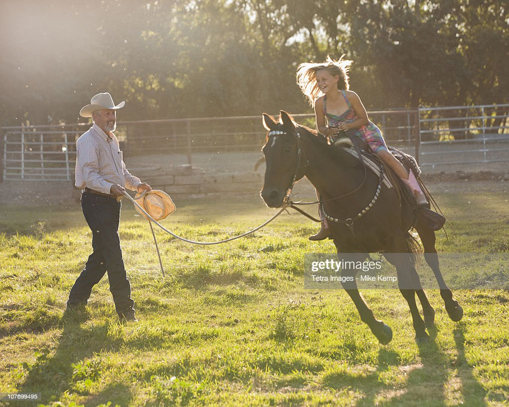 USA, Utah, Lehi, Trainer assisting girl (8-9) riding horse in paddock