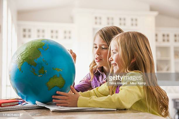 USA, Utah, Lehi, Two girls (6-7) doing homework with globe