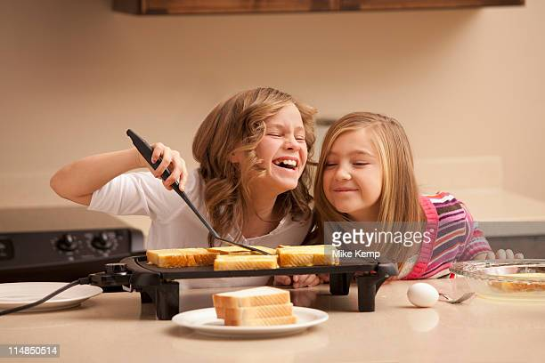 USA, Utah, Lehi, Two girls (10-11) preparing toast in kitchen