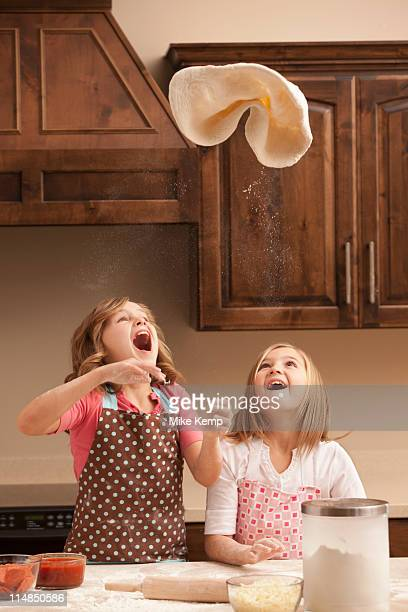 USA, Utah, Lehi, Two girls (10-11) tossing dough in kitchen