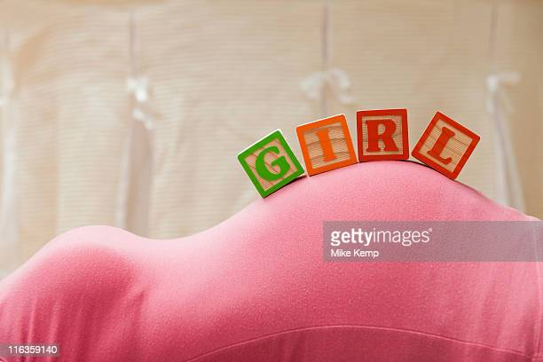USA, Utah, Lehi, Wooden blocks with letters on pregnant woman's belly, reading as girl