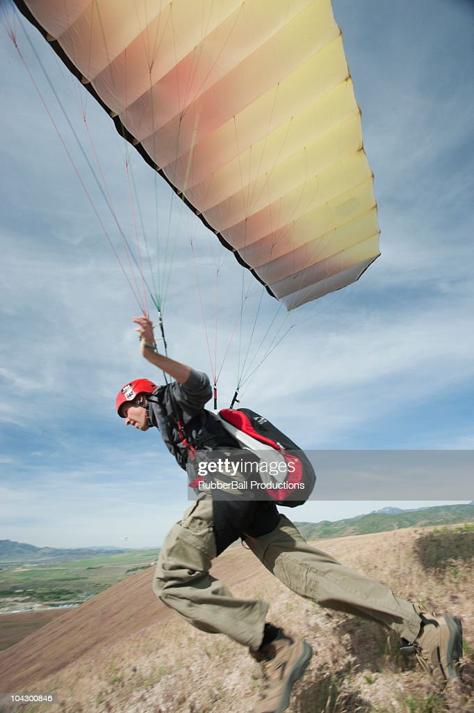 USA, Utah, Lehi, young paraglider starting from hill