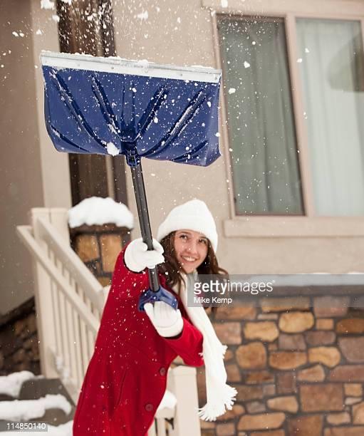 USA, Utah, Lehi, Young woman throwing snow using snow shovel